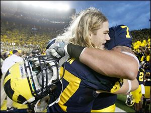 Michigan players Jake Ryan, left, and Taylor Lewan, 77,celebrate after the Wolverines defeat of Michigan State University.