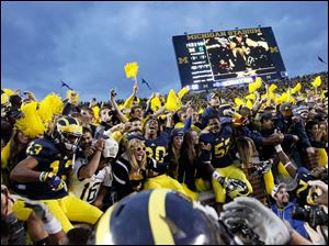 Michigan players celebrate in the student section after beating Michigan State 12-10 at Michigan Stadium in Ann Arbor.