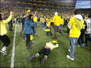 Michigan students celebrate on the field after the Wolverines defeat Michigan State.