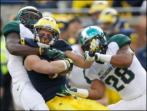 Michigan's Drew Dileo, 9, picks up a first down before being tackled by Michigan State University players RJ Williamson, 26, and Denicos Allen, 28.