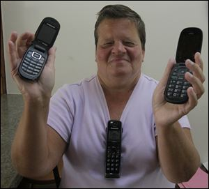 Betty Kasubski, of Maumee, who is blind, with the three phones she always wants with her, a cell, landline, and work phone.