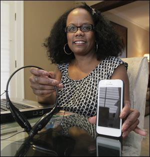 Darlene Whitehead, self-described phone addict, with her iPhone 5 and a bluetooth and radio device. She says she always has her phone or bluetooth at hand, whether she's at her computer, vaccuuming or doing other things around the house.