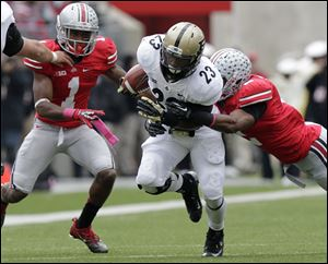 Purdue running back Ralph Bolden, center, runs the ball between Ohio State defensive back Bradley Roby, left, and defensive back Christian Bryant during the second quarter of an NCAA college football game Saturday.