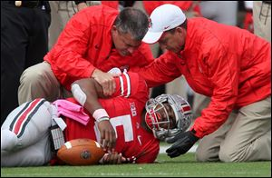 Ohio State Buckeyes quarterback Braxton Miller grimaces in pain as he is helped by trainers after getting injured in the third quarter.