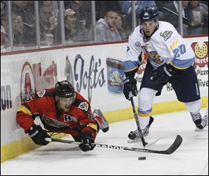 Phil Rauch, 20, knocks down Cincinnati Cyclones player Dan Eves, 16, as they battle behind the Walleye net.