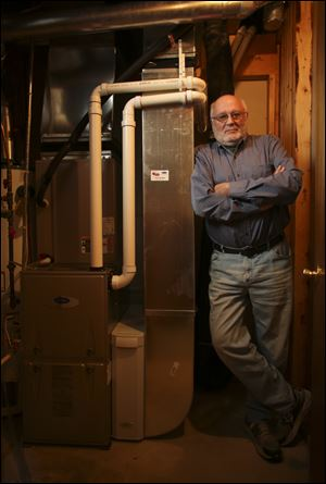 Allan Hoffman stands with his new, high efficiency furnace that will meet new federal standards coming next May, in the basement of his Coon Rapids, Minnesota home.