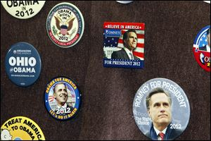 A collection of political buttons on display features Obama and Romney prominently in front of the display case at the Elyria Public Library.
