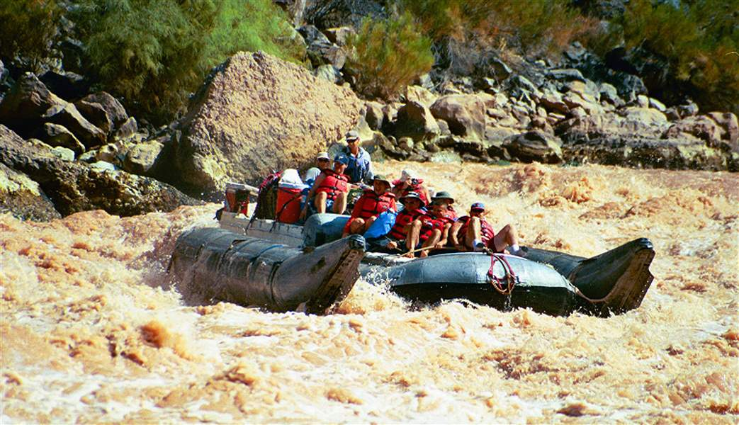 Visitors-ride-a-pontoon-raft-through-rapids
