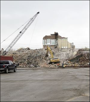 A wrecking crew reduces the former Longfellow Elementary School on Jackman Road to rubble. A new Longfellow opened this year on Laskey Road west of Jackman. The fireplace in the old building was preserved. It was incorporated into the new building's library.