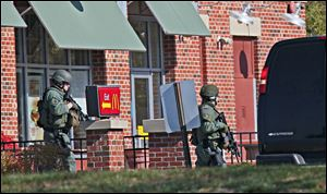 Tactical team members move past a McDonald's on the way to spa next door where, police say multiple people were wounded when someone opened fire, near the Brookfield Square Mall in Brookfield, Wis., Sunday.