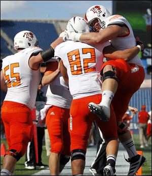 Bowling Green wide receiver Kevin Collins (82) celebrates his touchdown with teammates offensive linesman Alex Huettel (55) and offensive linesman Jordon Roussos, right, Saturday in Foxborough, Mass.