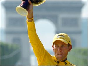 Lance Armstrong holds the winner's trophy after claiming his seventh straight Tour de France cycling race during ceremonies on the Champs-Elysees avenue in Paris July, 2005.