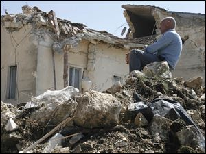 A man sits on rubble in the village of Onna, a day after a powerful earthquake struck the Abruzzo region in central Italy in April, 2009.