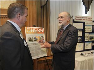 Roger Shope of Bowling Green, a TMACOG member and member of the Ohio Higher Education Rail Network, left, speaks with Thomas C. Carper, chair-man of the board, before the forum at the Toledo Club.
