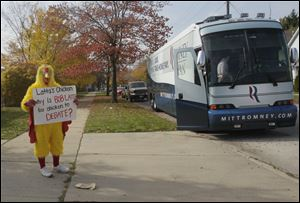 "A man in a chicken suit holds a ""Latta's Chicken"" sign near a Mitt Romney campaign bus across from the early voting poll location in Toledo."