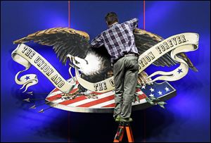 A worker adjusts the backdrop on stage in preparation for Monday's presidential debate between President Barack Obama and Republican presidential candidate, former Massachusetts Gov. Mitt Romney Sunday, at Lynn University in Boca Raton, Fla.