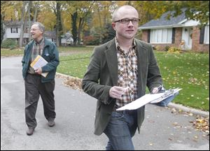 Denis Eble, left, and Evan Morrison head down Brookhurst Road in Sylvania as they go door to door on behalf of President Obama's re-election campaign. Crystal Bowersox also campaigned for the President last weekend.