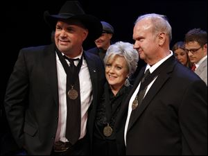 "Garth Brooks, left, Connie Smith, center, and Hargus ""Pig"" Robbins pose for a photo at the Country Music Hall of Fame Inductions."