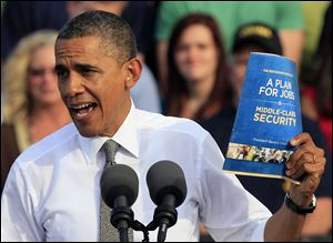 President Barack Obama holds up a copy of job plan during a joint campaign appearance with Vice President Joe Biden.