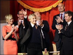 Entertainer Ellen DeGeneres, second from front left, waves as she is introduced, with wife Portia de Rossi, left, Monday before DeGeneres receives the 15th annual Mark Twain Prize for American Humor at the Kennedy Center.