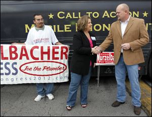 Amy Kremer, chairman of the Tea Party Express, shakes hands with Samuel Wurzelbacher in front of the Tea Party Express bus on Tuesday.