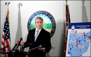 Ohio Auditor Dave Yost goes over the School Attendance Data Interim Report during a press conference in his Columbus office.
