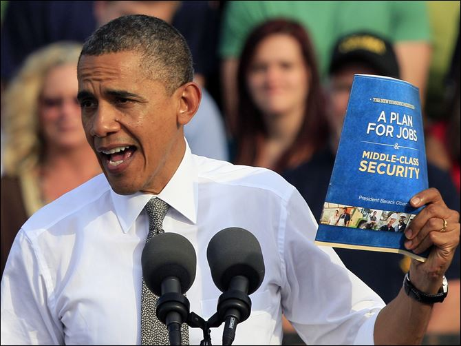 President Barack Obama holds up a copy of his jobs plan during a campaign appearance Tuesday in Dayton.