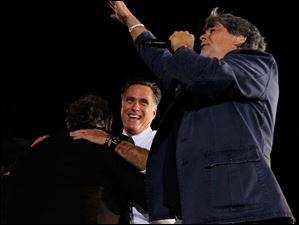 Republican presidential candidate Mitt Romney hugs Meatloaf as musician Randy Owen waves to the crowd.