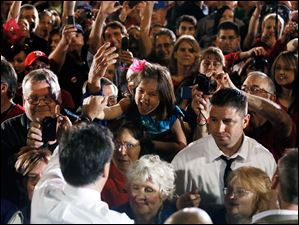 Republican presidential candidate Mitt Romney greets a young supporter during the rally.