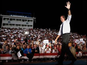 Republican presidential candidate Mitt Romney waves on stage.