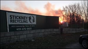 The sun rises behind Stickney Recycling Plant, as a fire smolders in the distance.