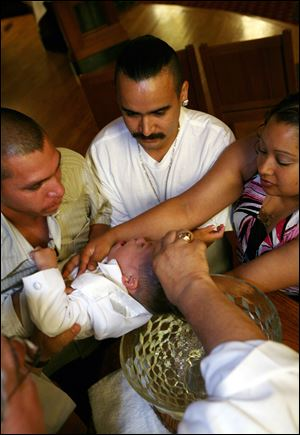 Jose Correa, left, is joined by Daniel and Esmeralda Barrera at the baptism of Mr. Correa's 2-year-old son, Osbaldo. Mr. Correa was among 101 Latino workers terminated by WinCup in March.