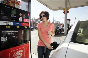 Tori Turner, of Sylvania Township, tops off her tank at the Speedway at Laskey and Secor in Toledo. Gas prices have fallen to below $3.00 per gallon at several  stations in Toledo
