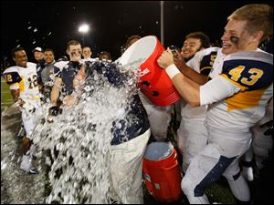 Whitmer head coach Jerry Bell is drenched by Whitmer Robert Sobecki (43) after defeating Central Catholic.