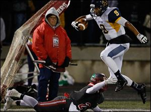 Whitmer's Christopher Boykin (9) makes a catch against  Central Catholic's Derich Weiland (24).