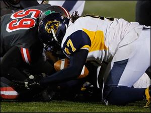 Whitmer's Al Bryant (47) recovers a fumble by Central Catholic's Paul Moses (5).