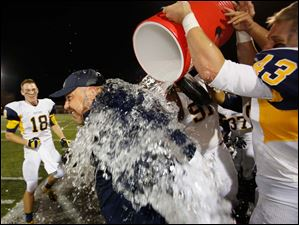 Head coach Jerry Bell is splashed with water by Whitmer's Robert Sobecki (43) after a 42-0 win over Central Catholic.