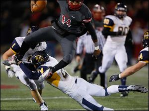 Irish quarterback Deshone Kizer (14) leaps over  Whitmer's Elijah Elliott (34).