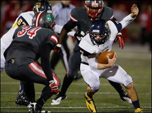 Whitmer's quarterback Nick Holley (7) runs the ball  against  Central Catholic's Ian Butler (34).