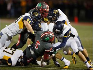 The Whitmer defense shuts down Central Catholic's Paul Moses (5).