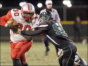 Bowsher senior Pharaoh Reid attempts to hold off a Start defender while rushing during the first half at Start.