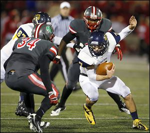 Whitmer's Nick Holley tries to elude Central Catholic's Ian Butler. Holley rushed 22 times for 122 yards and two touchdowns. He threw for two more touchdowns.