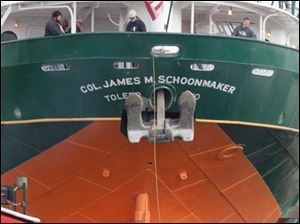 The tug Mississippi unties from the S.S. Col. James M. Schoonmaker as the Great Lakes freighter nears its new mooring in the shadow of the Veterans' Memorial Skyline Bridge.