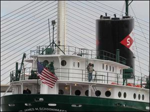 The S.S. Col. James M. Schoonmaker is tugged back to its new mooring in the shadow of the Veterans' Memorial Skyline Bridge.