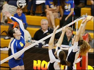 St. Ursula's Katie McKernan (5) spikes the ball against  Notre Dame's Stefanie Comte (7) and Christy Ohlinger (13).
