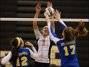 Notre Dame's Payton Bowyer (1) battles St. Ursula's Morgan Finn (17) and Lauren Daudelin (12) at the net.