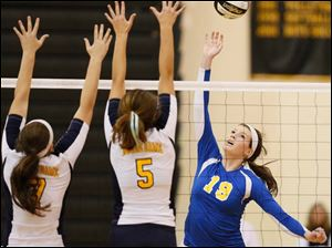 St. Ursula's Maddie Burnham (19) hits the ball against  Notre Dame's Stefanie Comte (7) and Madeline Smyth (5).