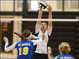 Notre Dame's Madeline Smyth (5) hits the ball against St. Ursula's Maddie Burnham (19) and Ryann Cox (4).