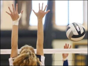 St. Ursula's Katie McKernan (5) hits the ball against Notre Dame's Christy Ohlinger (13).