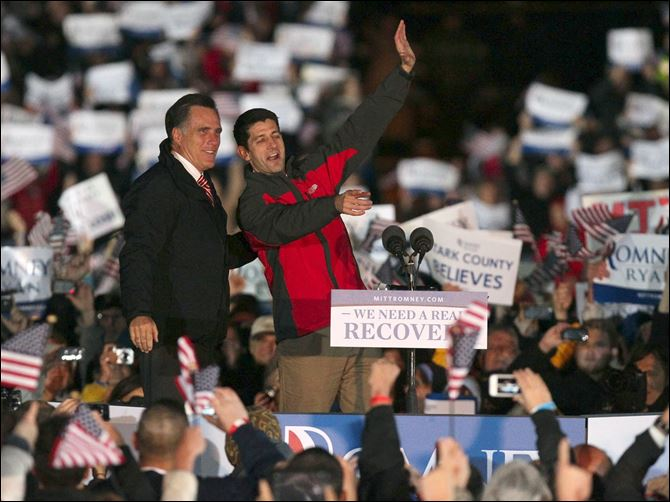 Republican presidential candidate Mitt Romney (left) and his running mate Rep. Paul Ryan, R-Wis. wave to supporters Friday at North Canton Hoover High School in North Canton.